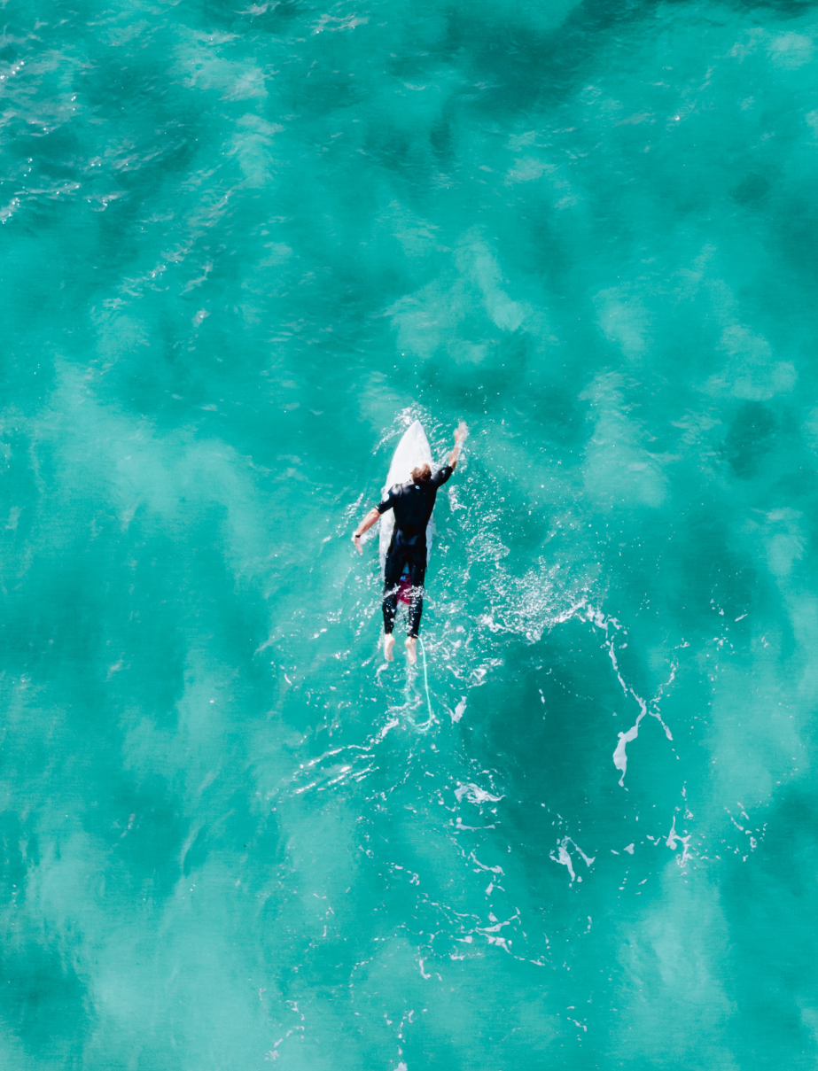 Person paddling out to sea on surfboard