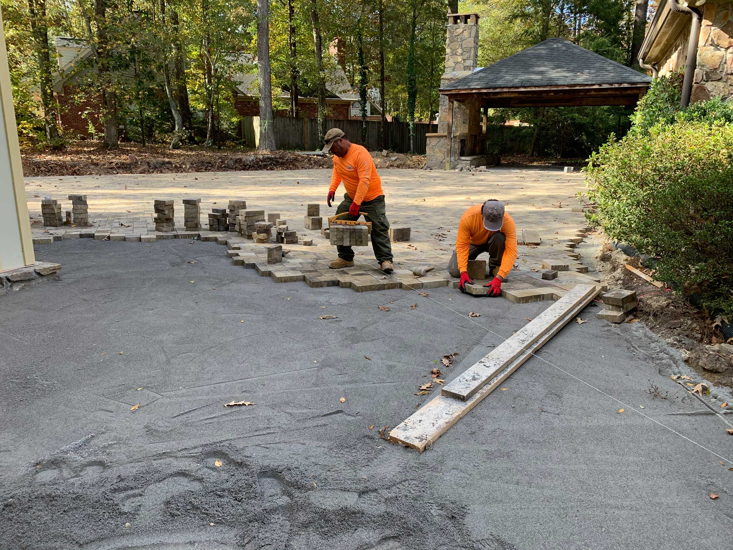 Two workers lay down paving stones
