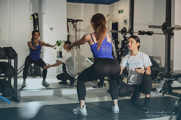 woman is doing squats with personal trainer
