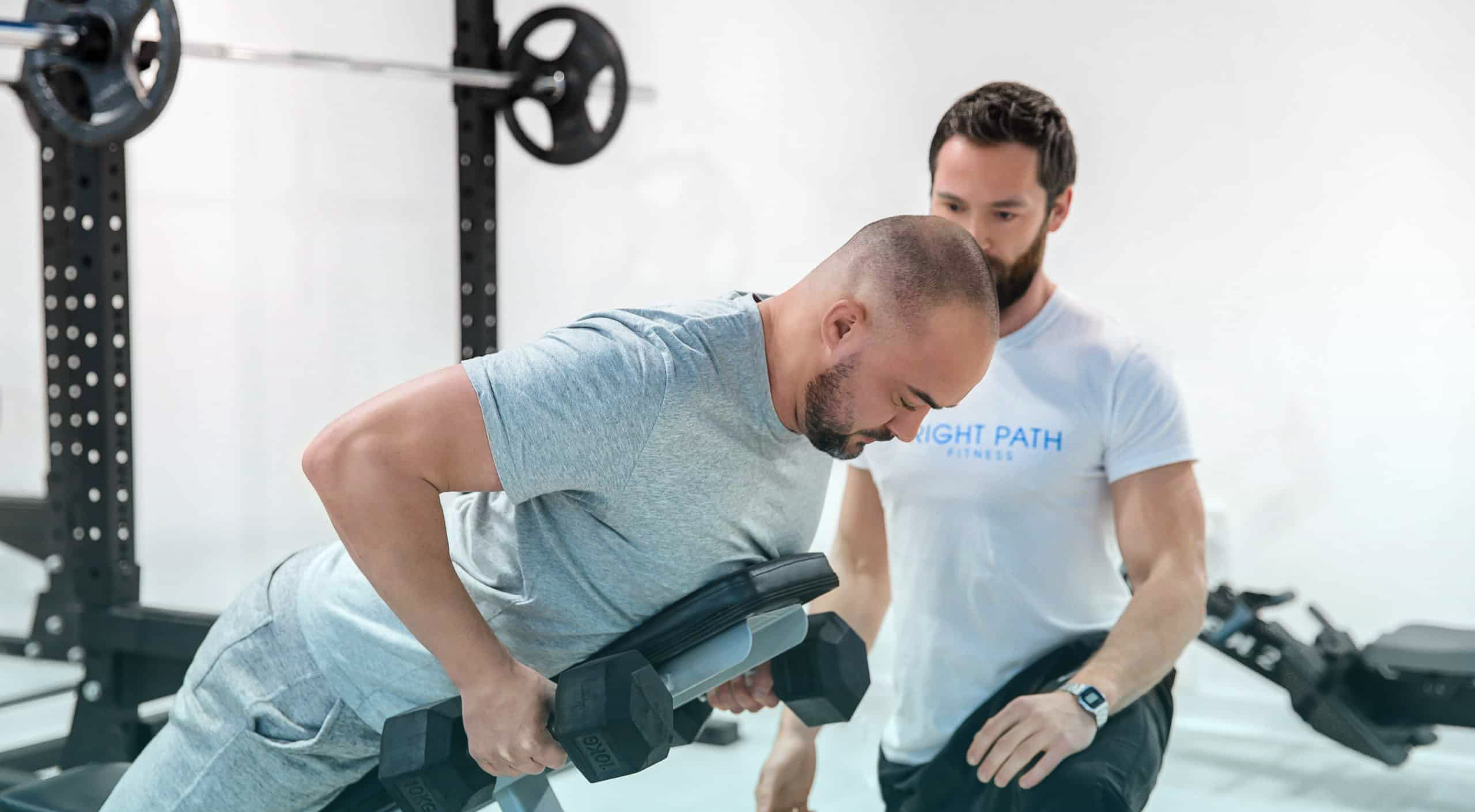Hyperextension with personal trainer in gym