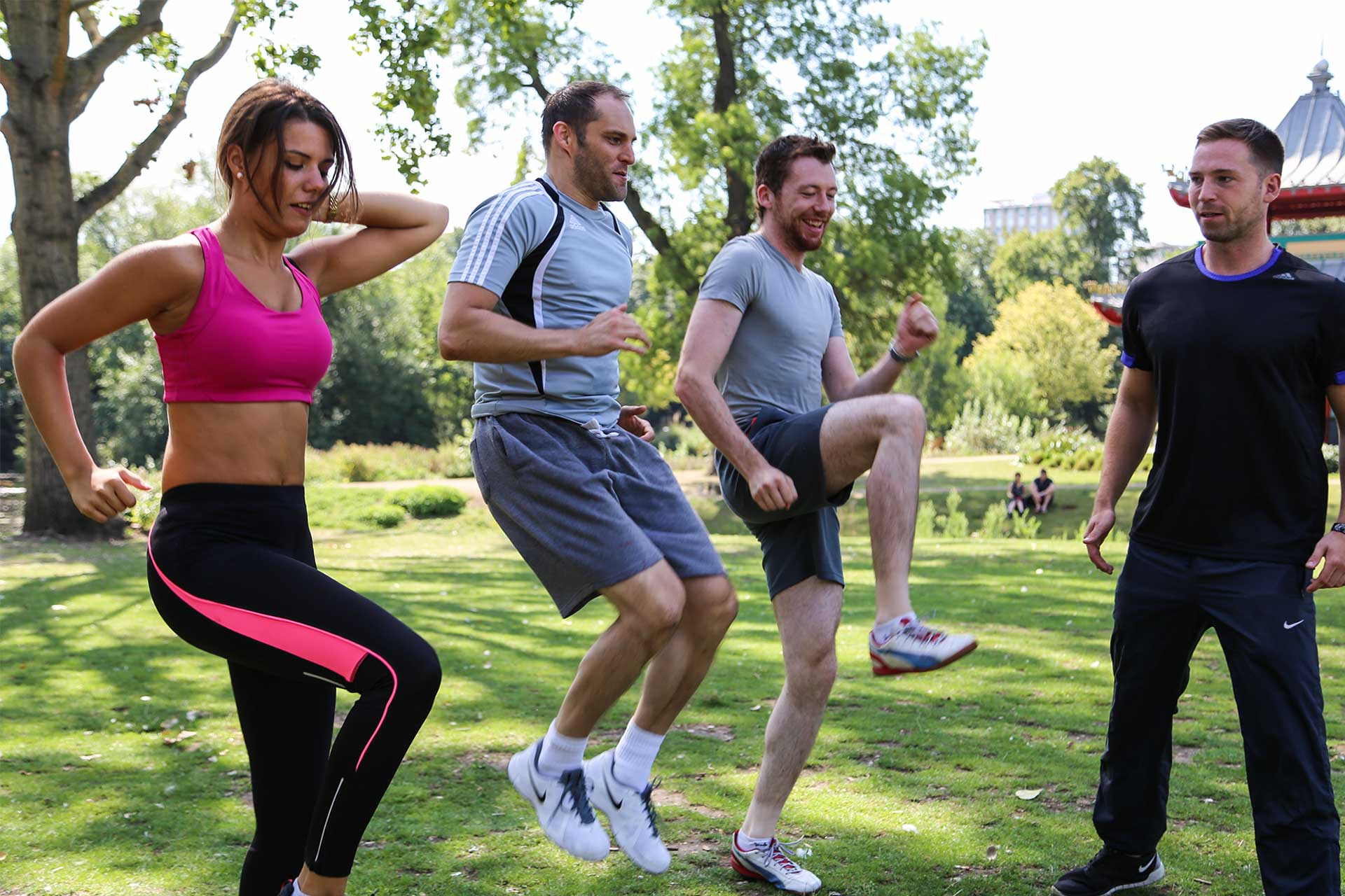 Outdoor exercises with friends and personal trainer in park