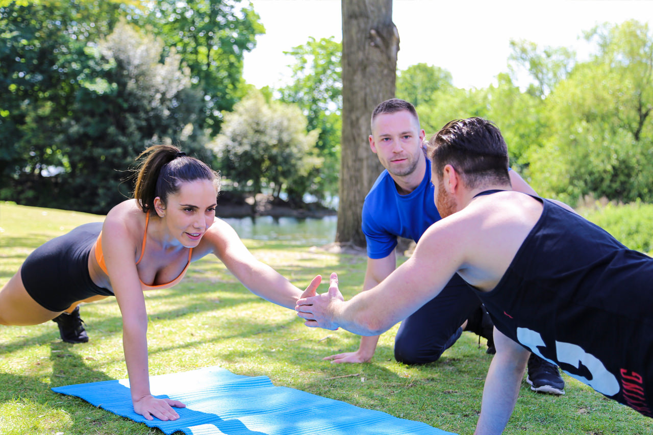 group workout with personal trainer in park