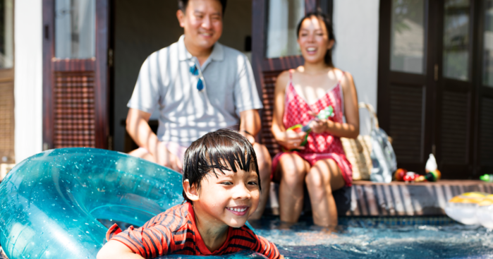 boy with parents swimming in a pool