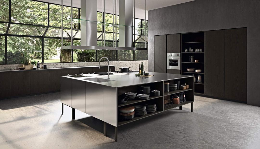Cucina moderna con isola centrale con piano e fianchi in acciaio e colonne contenitive