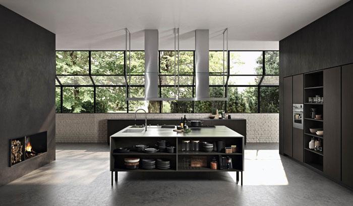 Cucina moderna scura con isola centrale funzionale con piano in acciaio e colonne contenitive con ripiani estraibili