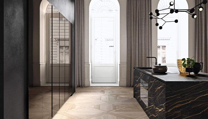 Cucina scura con penisola centrale scura con frontali neri effetto marmo e colonne con frontali in vetro fumè