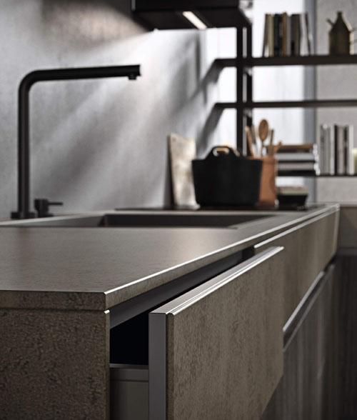 Cucina con gola in metallo e dettaglio cassetto sotto top in gres altezza 12 cm