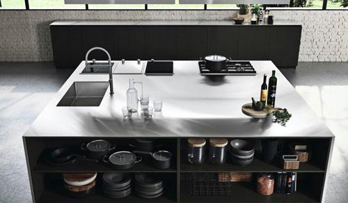 Cucina moderna scura con isola centrale e piano di lavoro in acciaio inox con lavello e piano cottura