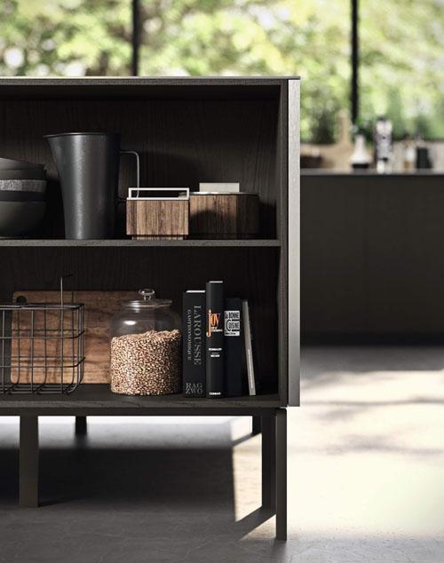 Cucina con isola centrale con piano lavoro e basi contenitive senza ante con piedini in metallo nero