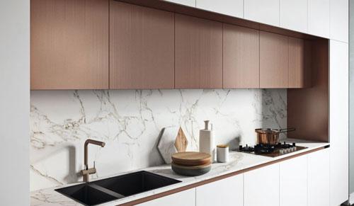 Cucina moderna bianca con pensili laccati rame e dettagli di lusso moderni