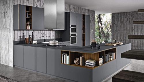 Cucina ad angolo con isola funzionale e ampio piano da lavoro e maniglie in finitura brunito