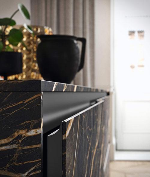 Dettaglio dell'anta con apertura a gola con telaio in alluminio nero e frontali in gres nero con effetto marmo
