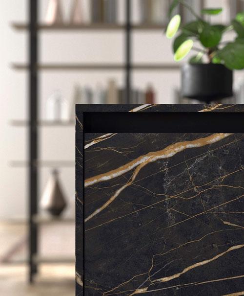 Cucina con isola centrale e dettaglio delle ante in gres nero effetto marmo con apertura a gola e telaio nero