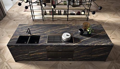 Cucina moderna scura con isola centrale con ante ad apertura con gola nera e top e frontali in gres