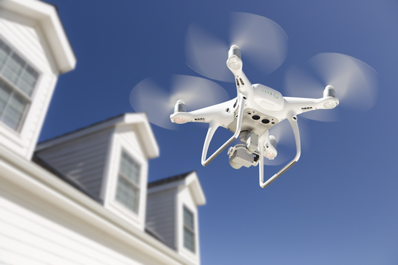 a drone in flight in front a blue sky and a modern white house