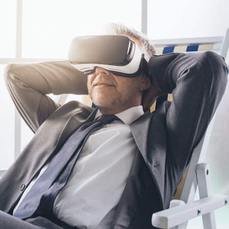 a man in business outfit laying back in his chair wearing VR glasses and holding his hands behind his neck in relaxed position