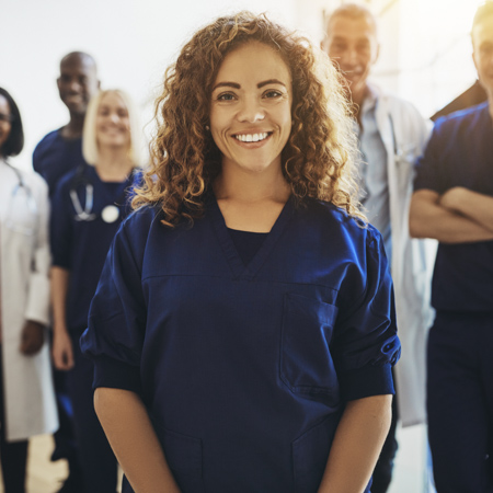 a diverse and happy team of medical personnel smiling towards the camera with female team member standing closer to the camera in front