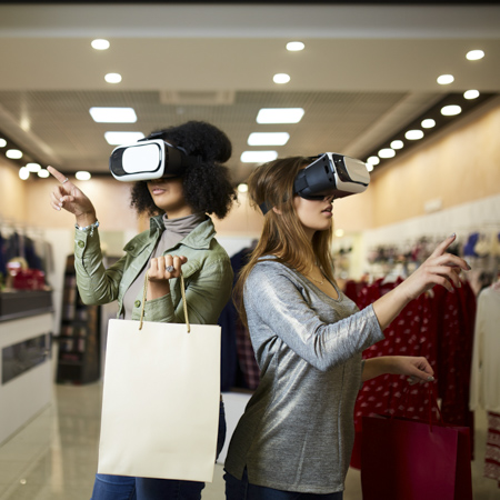 Two women within a fashion store wearing VR glasses gesturing in the air suggesting virtual VR shopping