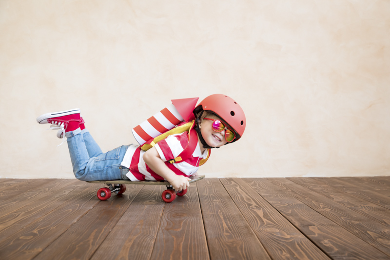 a young boy lying on a skateboard with helmet, googles, and an rocket attached to back