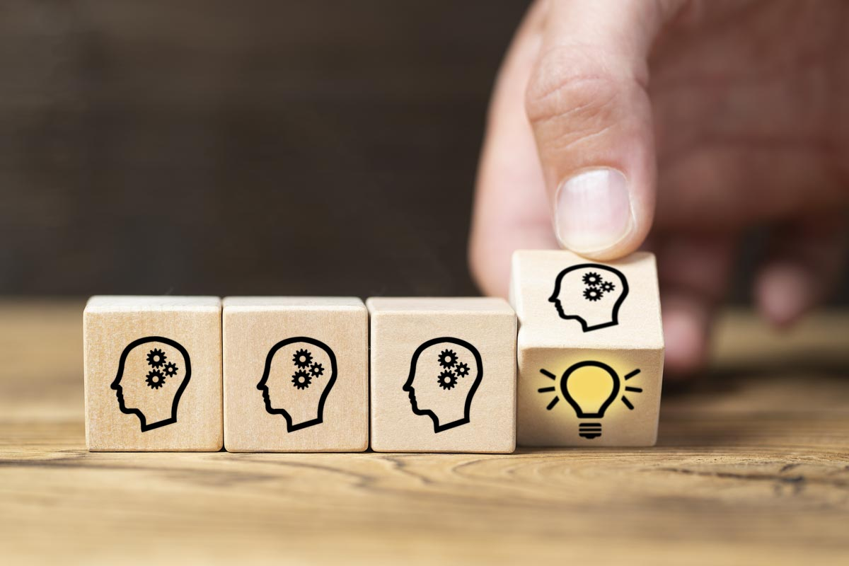 4 cubes on a desk showing an human think process icon, a male hand lifting the most rightest cube revealing a shining light bulb
