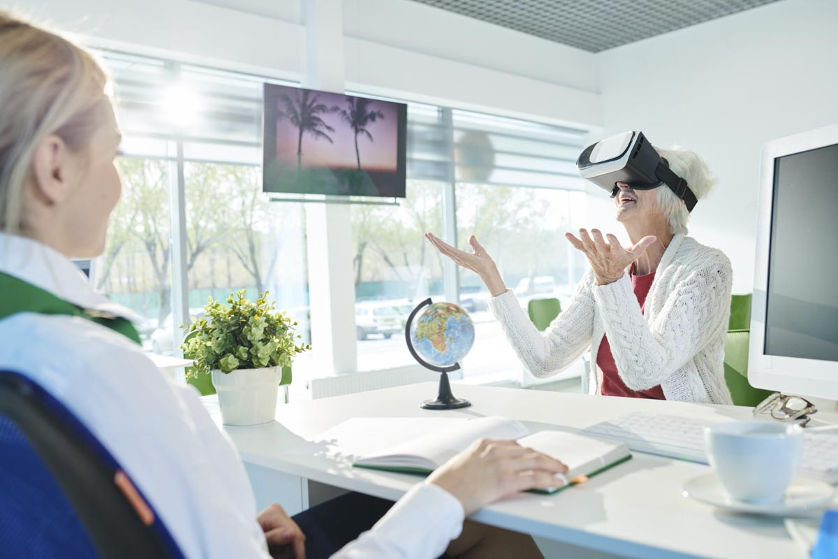 an elderly women wearing VR glasses in a travel agency enjoying a virtual experience with seeable joy and gestures