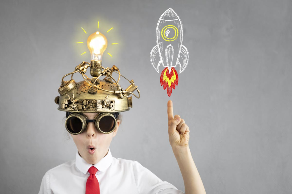 a boy wearing a mechanic helmet with shining light bulb lifting up the right hand with upwards pointing index finger towards a chalk painted rocket lifting towards sky suggesting a smart process for SEO services