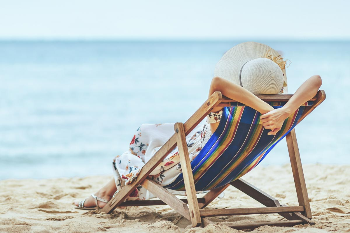 woman lying in a beach chair relaxing showed from behind in front of the waterfront