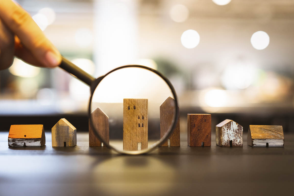 A magnifying glass observes a wooden toy house