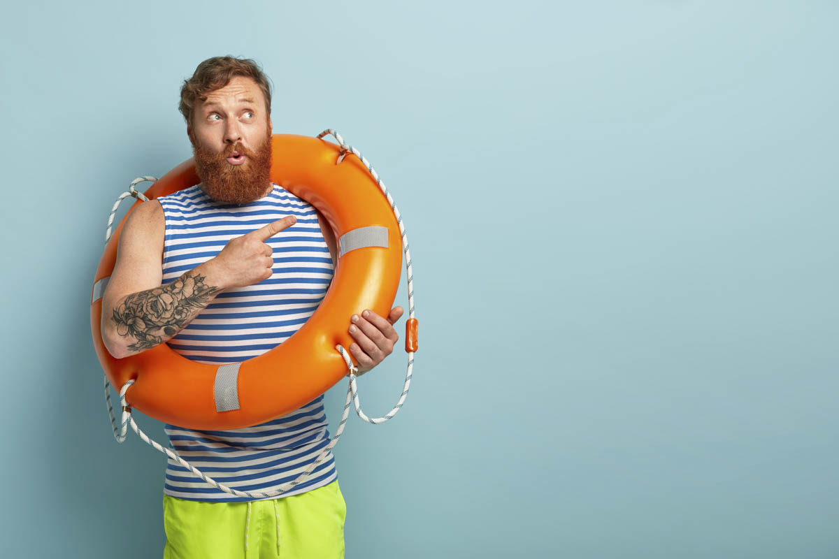 A man in sailor outfit wearing a lifebuoy pointing towards something