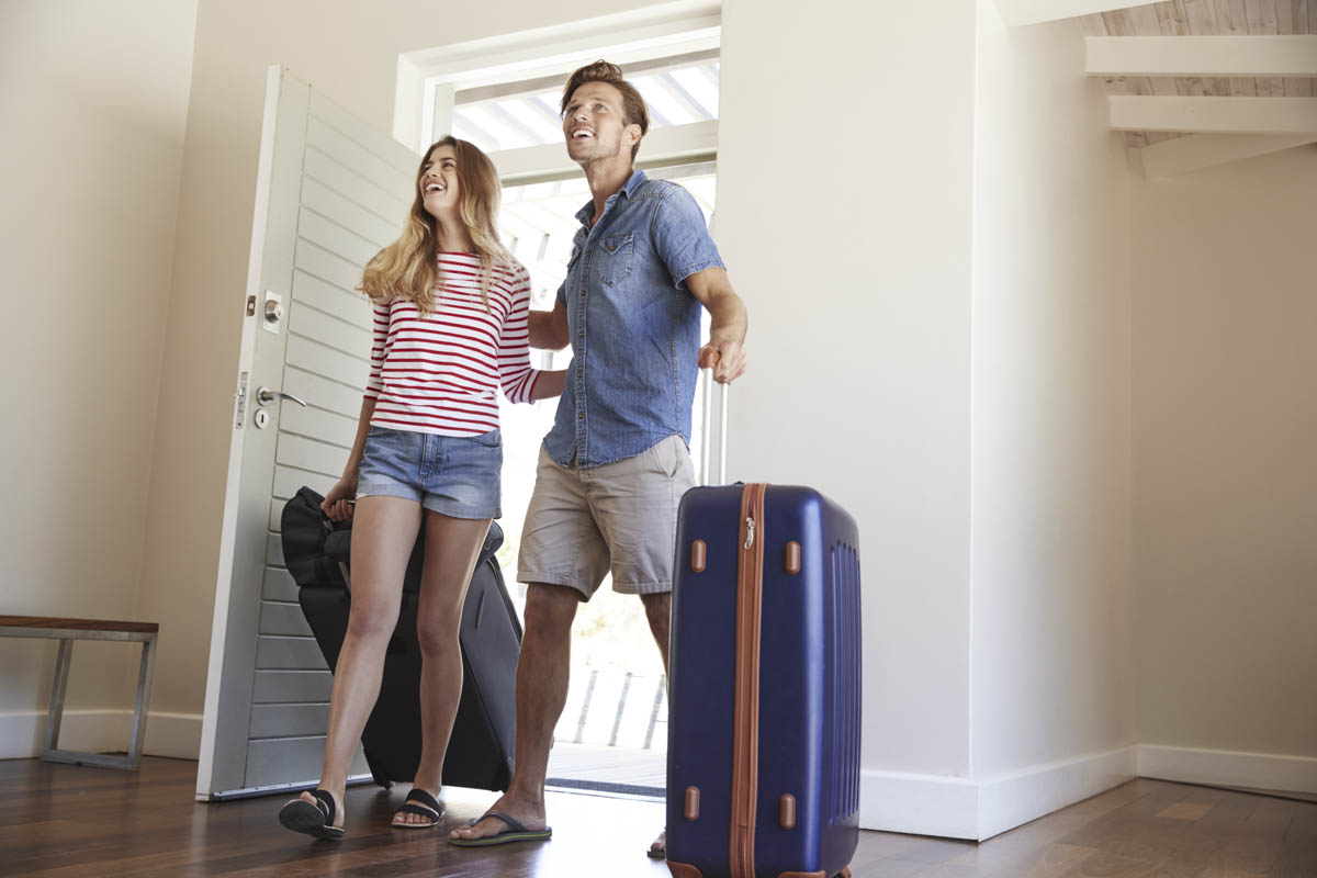 An happy couple with suitcases arriving at their holiday apartment