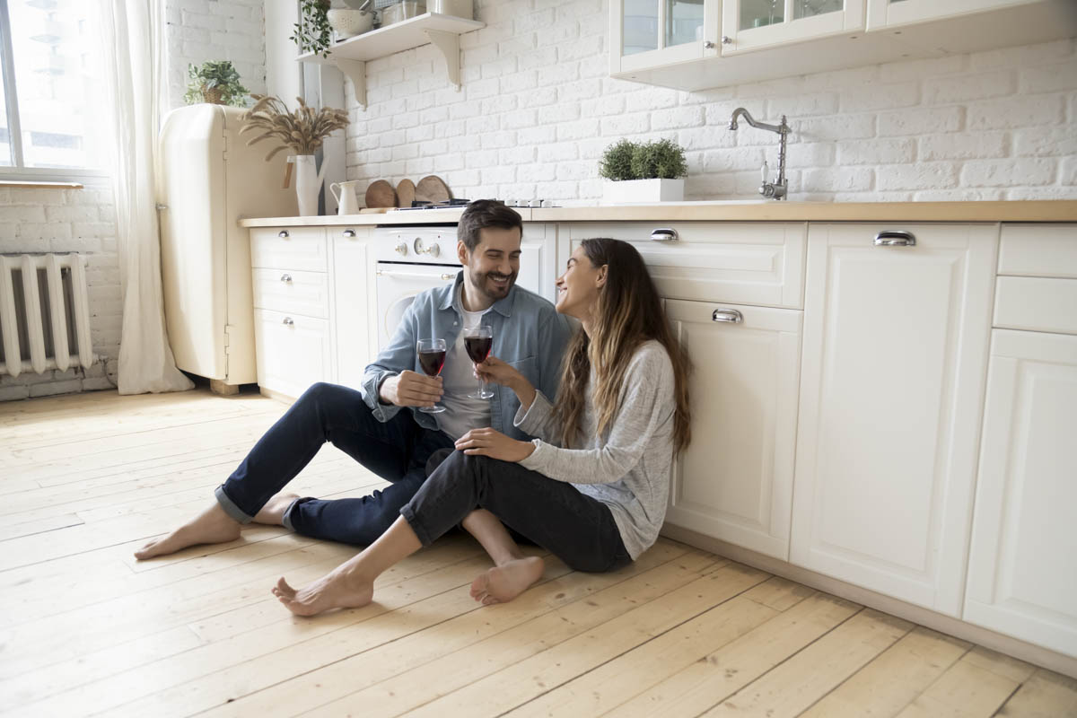 a couple sitting on the kitchen floor looking at each other smiling with a glass of wine in their hands