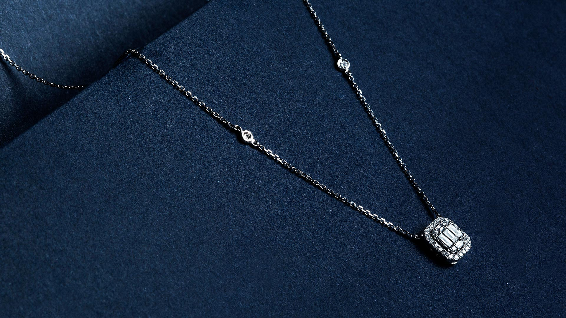 A white gold pendant on a blue background