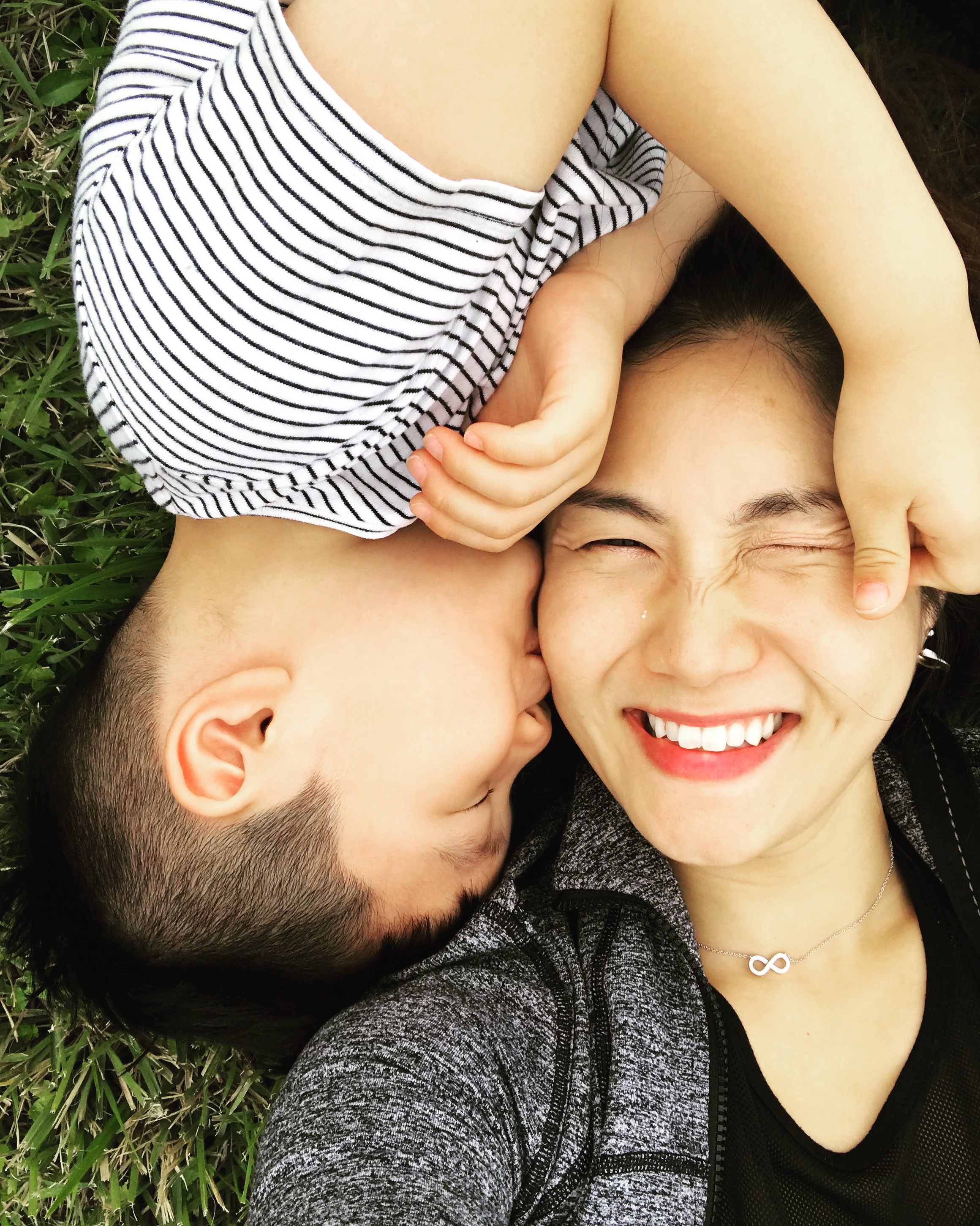 Grace with her son smiling and playing on the grass.
