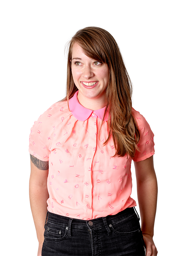 A photograph of Beth. Beth is a white woman with brown hair. She is wearing a pink button-up shirt with small letters on it, and black pants. She is looking off to the side and smiling. The image is trimmed to her silhouette and placed in front of a light pink background.