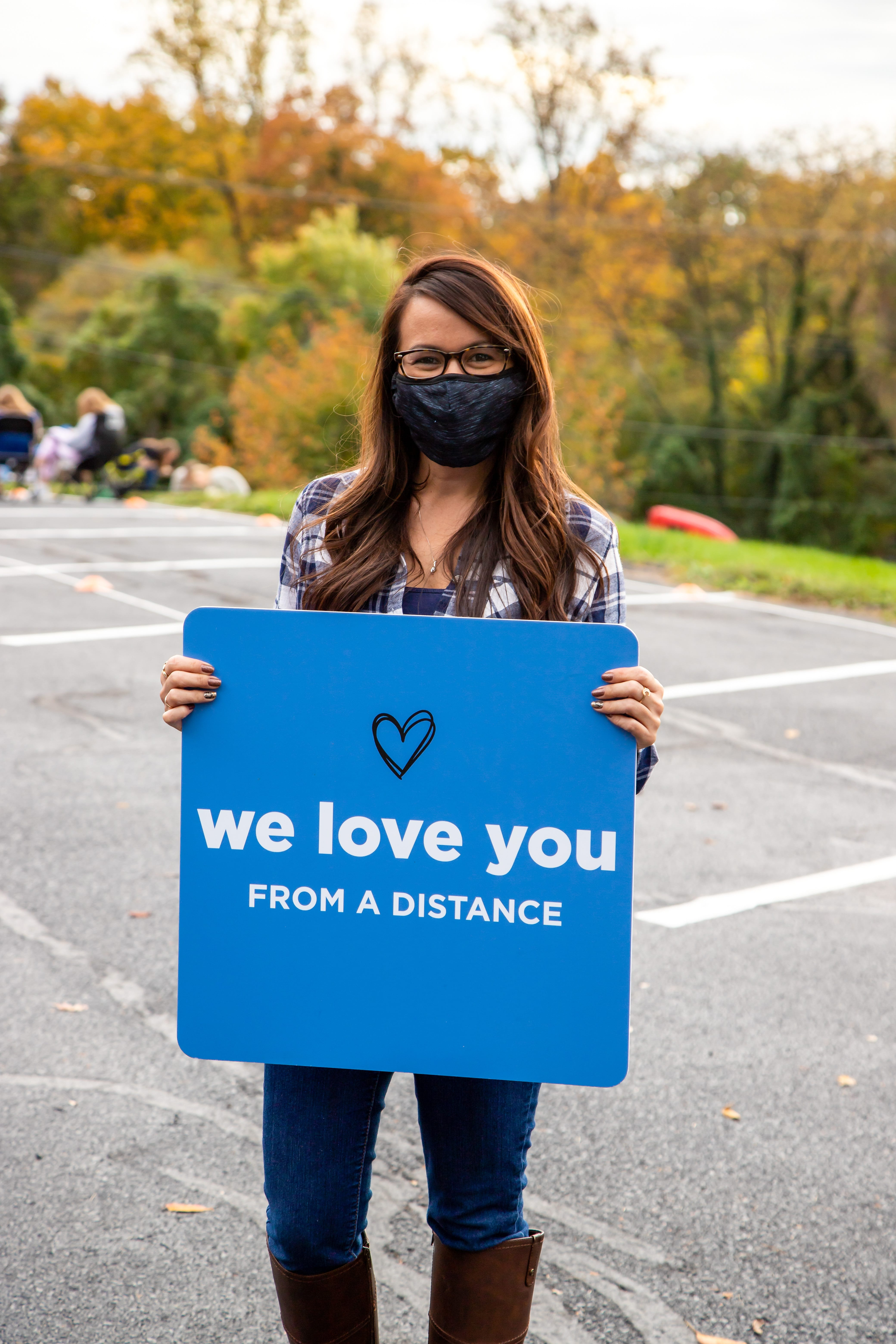A photo of a young women from catalyst holding a welcome sign