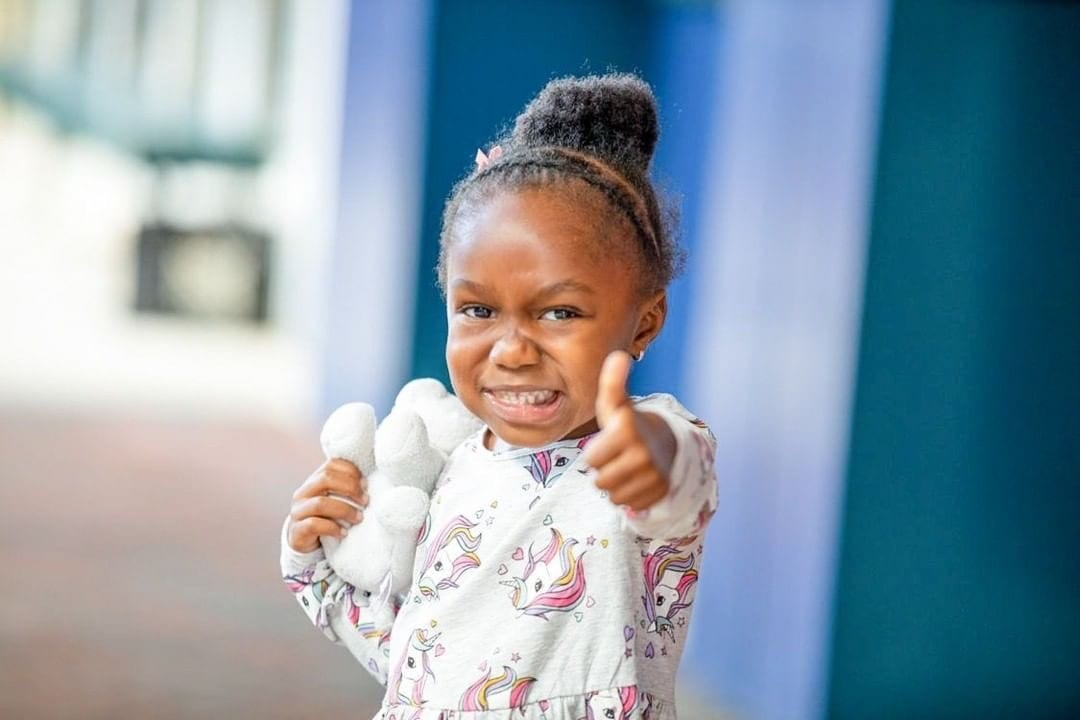 A photo of a child giving thumbs up.