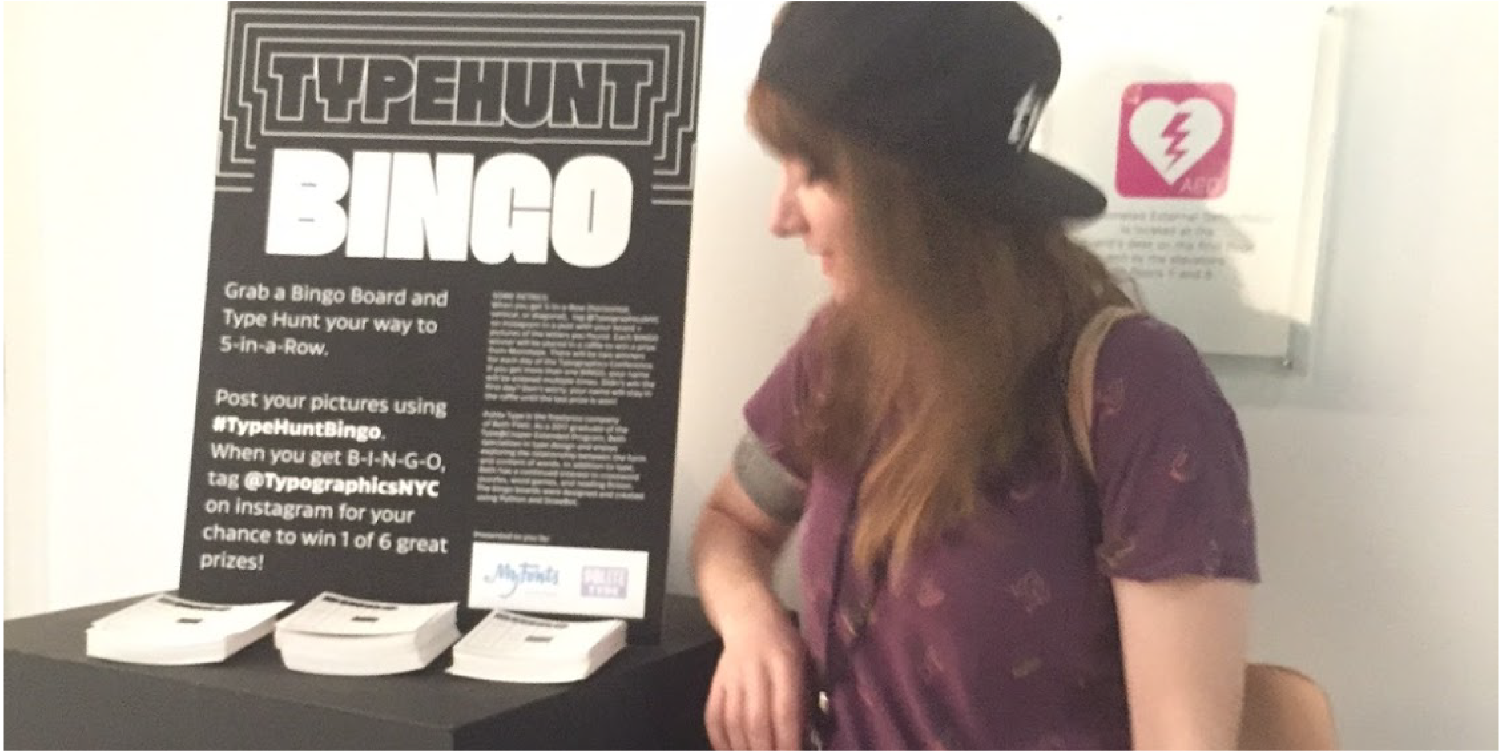 A photo of Beth, a white woman with brown hair and a backwards baseball cap, standing in front of a display for the TypeHuntBingo cards and a sign with instructions..