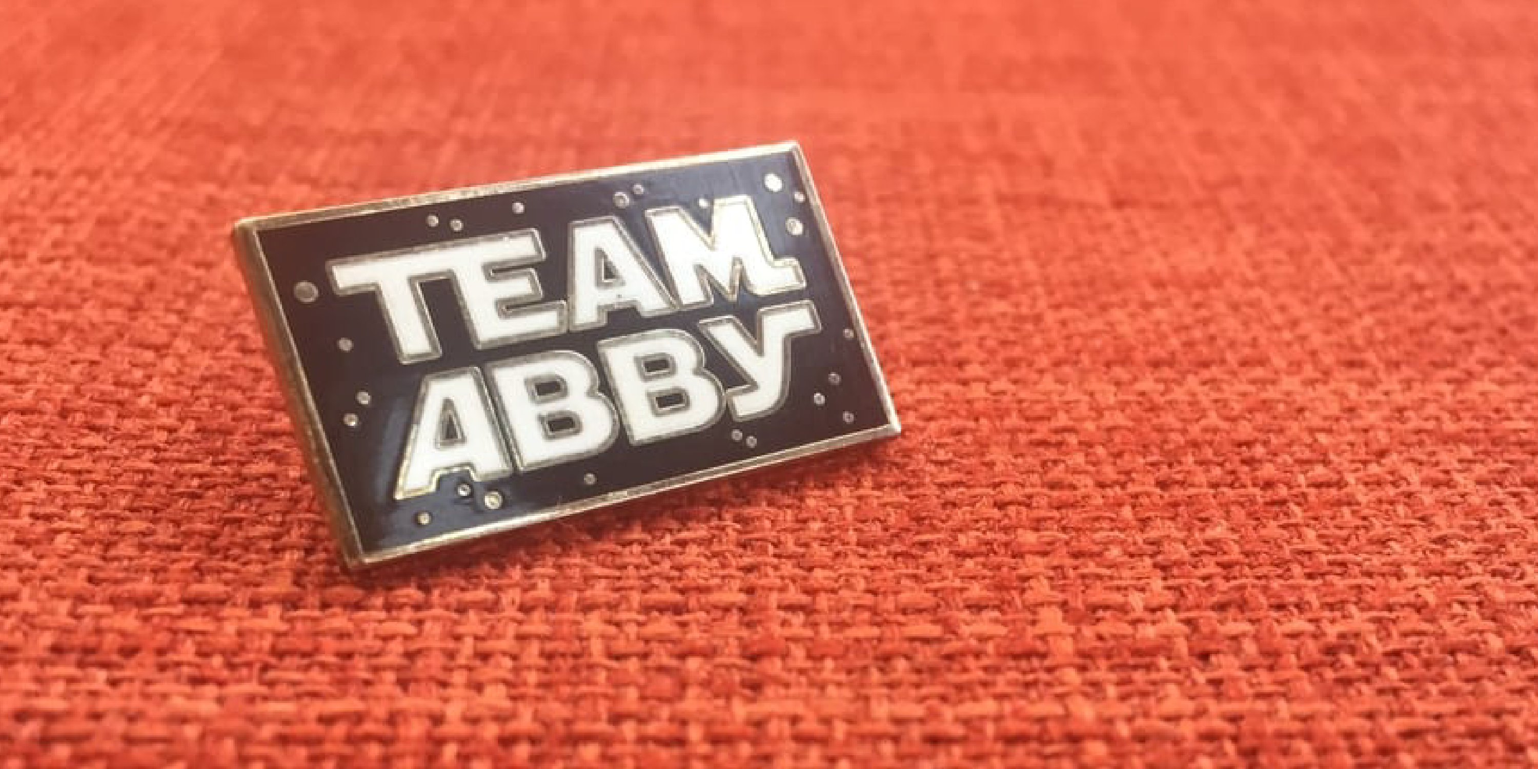"There is a lapel pin on an orange tablecloth. The lapel pin is black and has the text ""Team Abby"" drawn to look like the Star Wars logo."