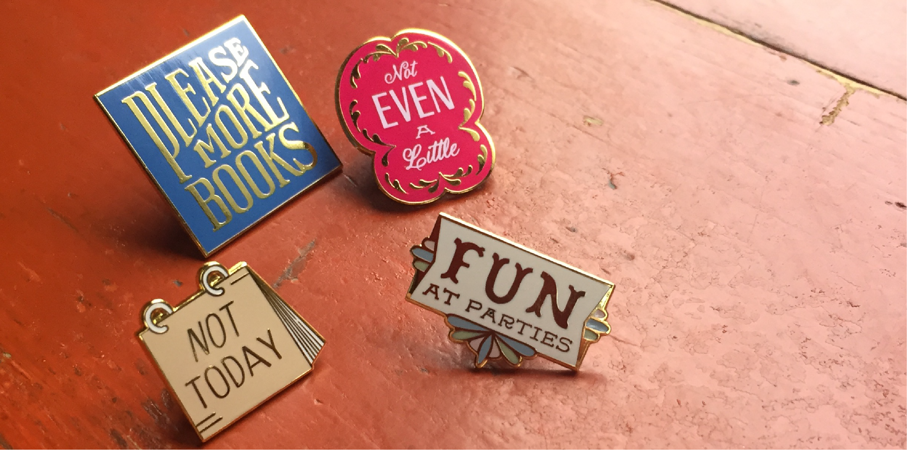 "This is a photograph of 4 pins on a wood table background. There is a blue pin that says ""Please More Books""; a red pin that says ""Not Even A Little""; a small calendar pin that reads ""Not Today"" and a small white pin that says ""Fun at Parties."""