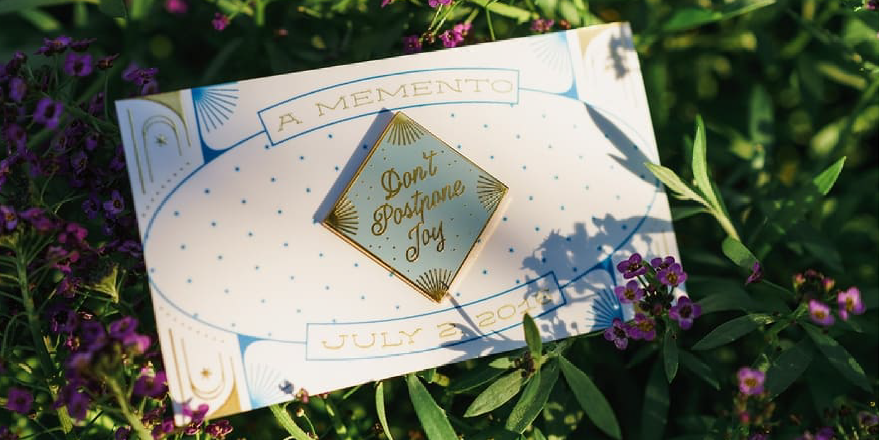 "There is a lapel pin pinned to a card. The card is sitting in lush greenery. The lapel pin is diamond shaped and light blue. The text on it reads ""Don't Postpone Joy."""