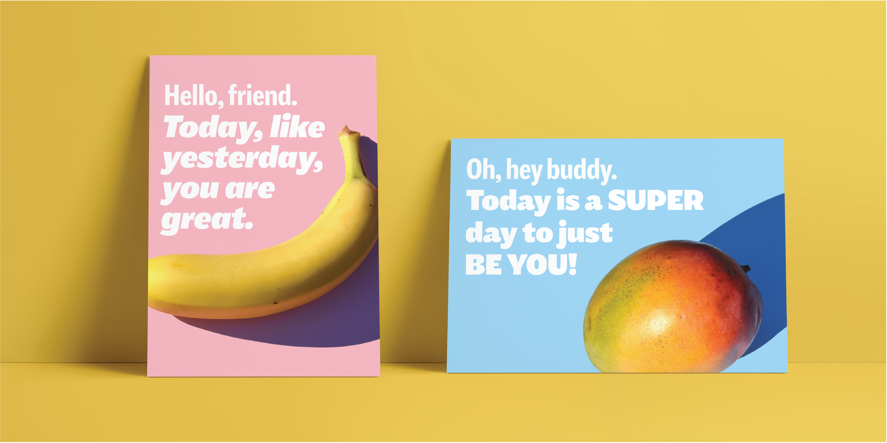 "A yellow background with two posters. The first poster is pink with a banana on it. The text reads ""Hello friend. Today, like yesterday, you are great."" There is a blue poster next to it. On the blue poster is an apple and the words, ""Oh hey buddy. Today is a super day to just be you."""