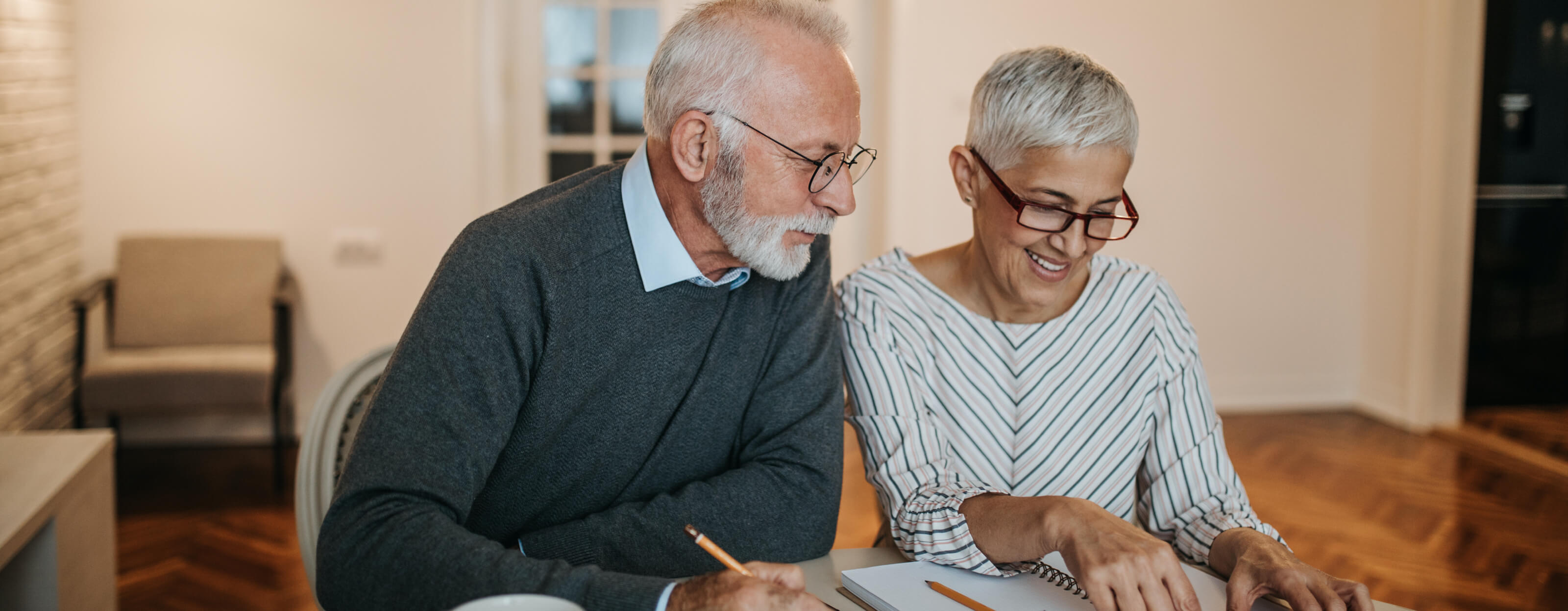 A retired couple sitting at a table reviewing documents