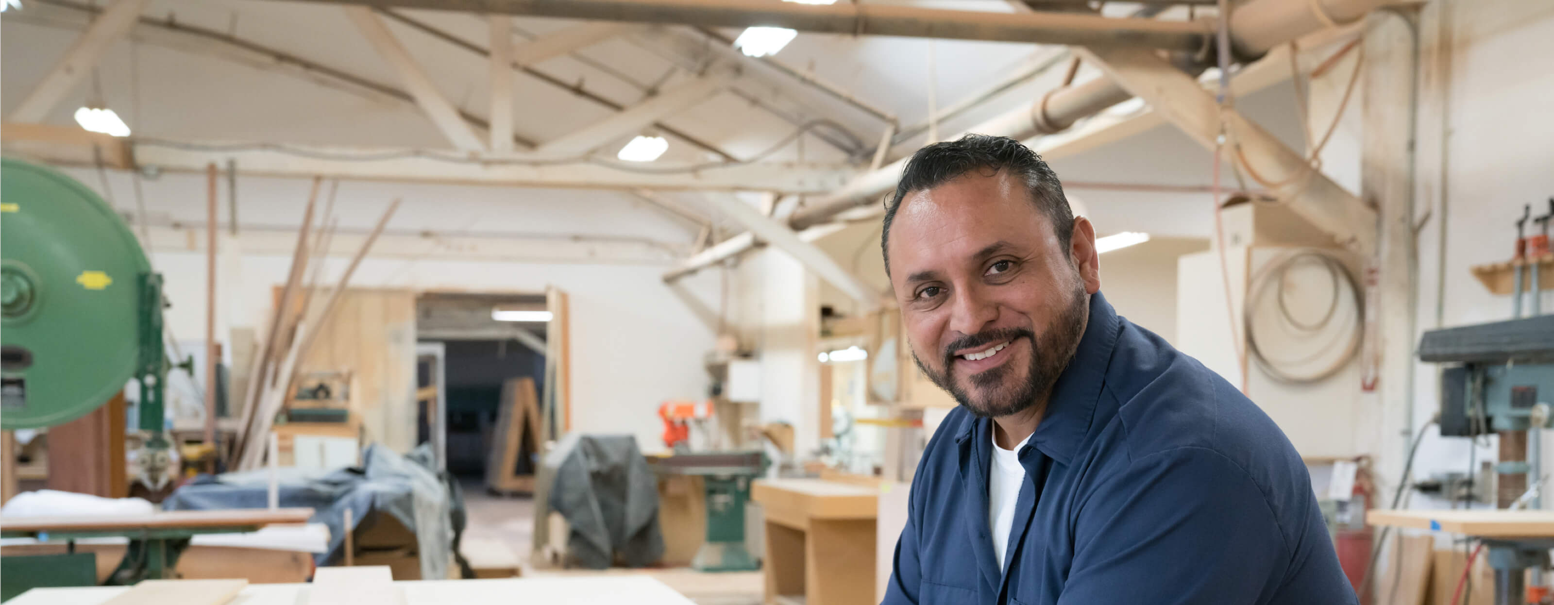 A smiling man sitting in a woodshop
