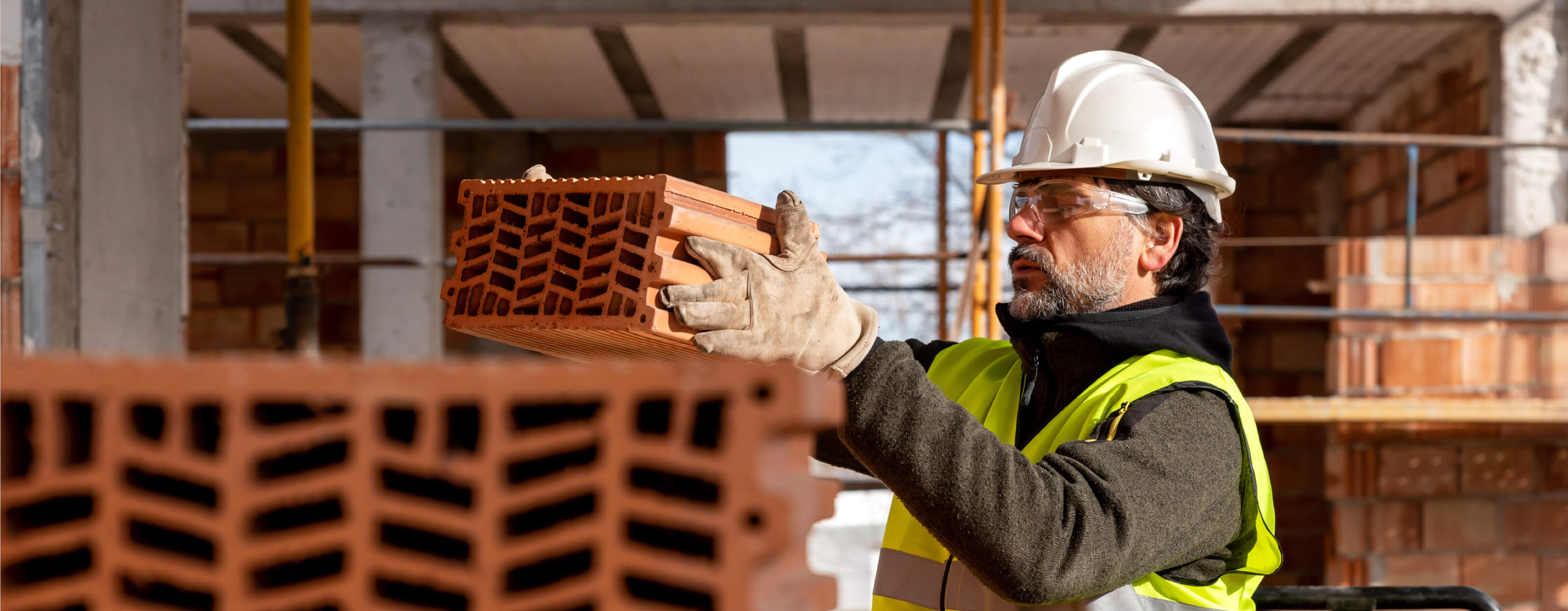 A construction worker wearing a hard hat moving heavy blocks