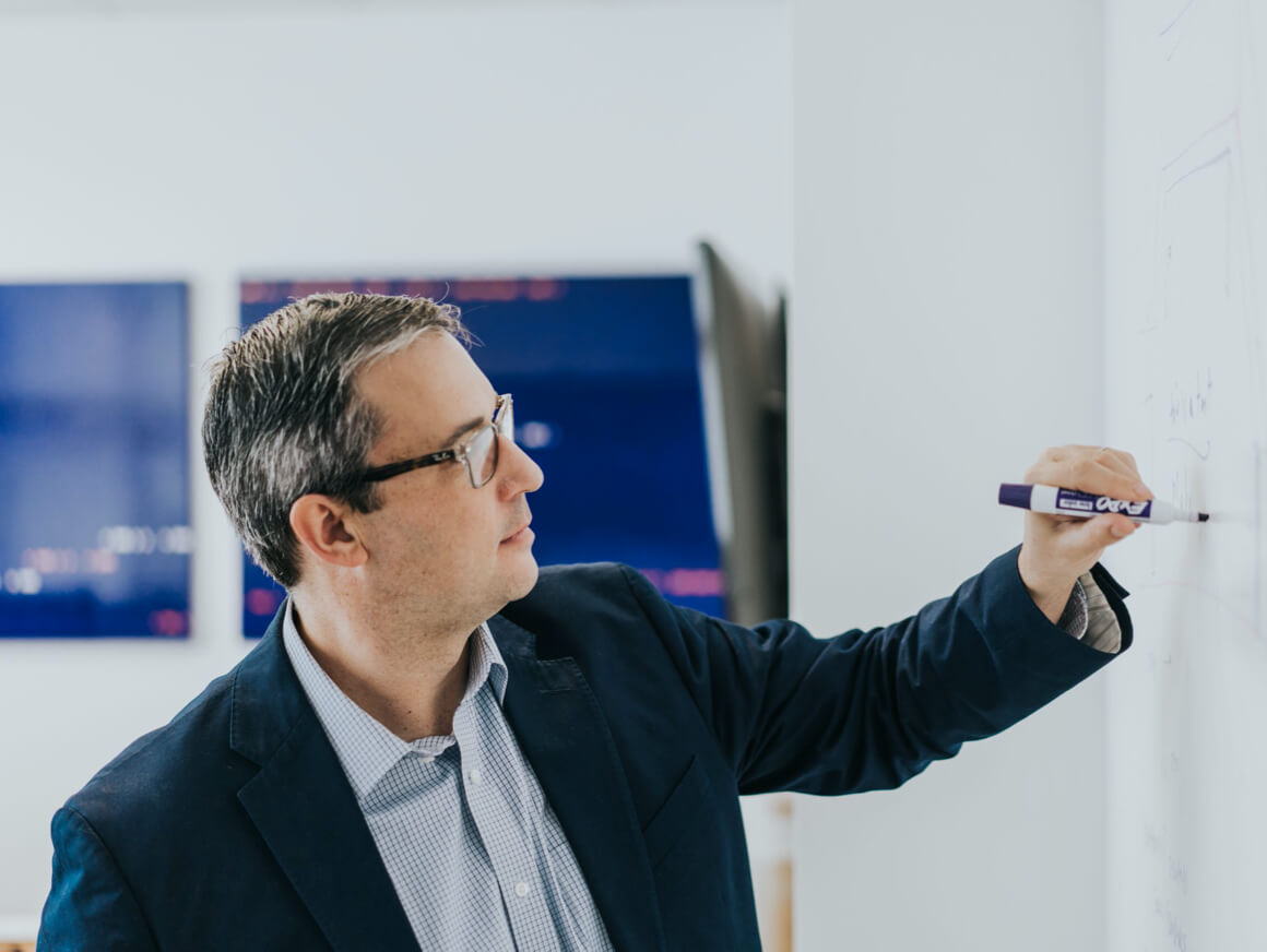 A man sketching ideas on a whiteboard