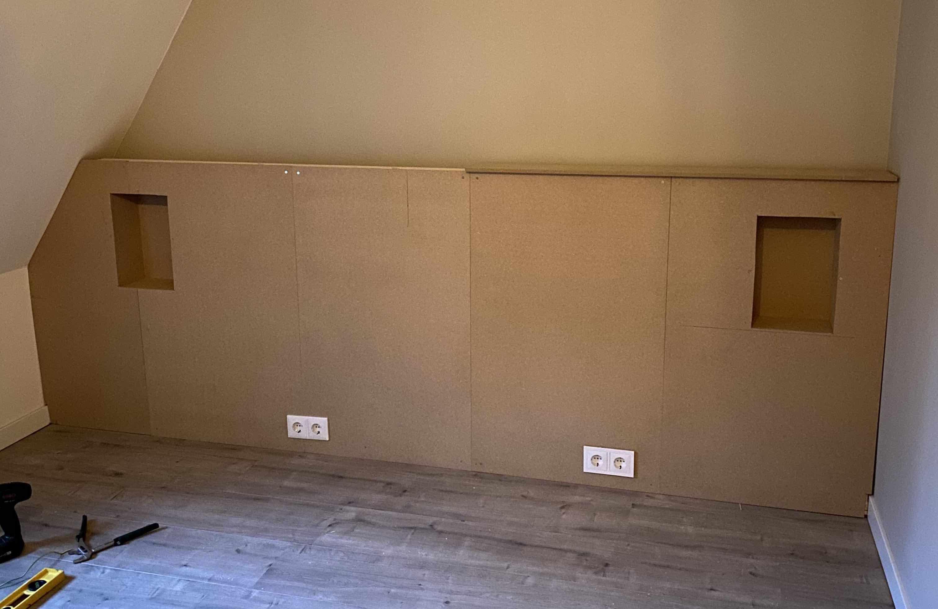 Hoofdbord met nisjes in de slaapkamer onder een schuine wand