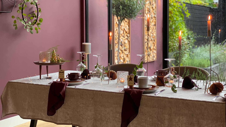 Tafel dekken voor kerst in lichtgrijs met aubergine kleurige servetten