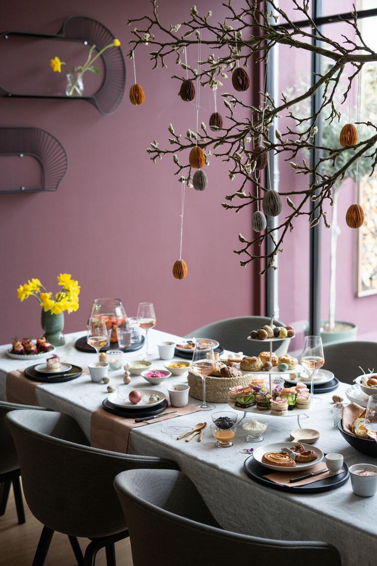 DIY magnolia-tak boven de paastafel met papieren eieren in verschillende kleuren van Department Delight