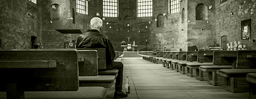 A old priest sitting in an empty church.