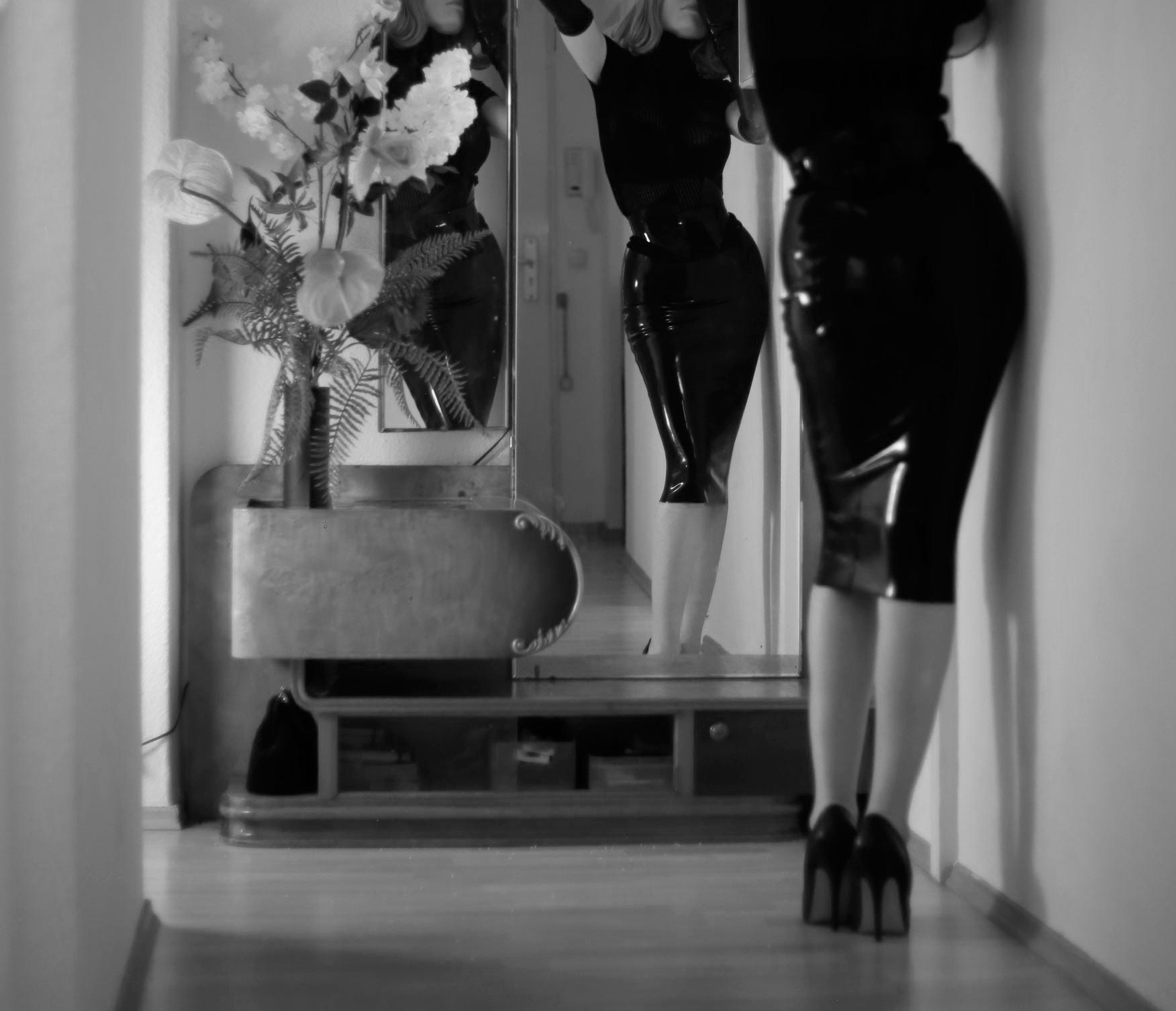 A long, high-waisted pencil wiggle skirt in black latex rubber.